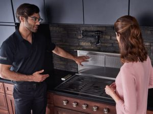 Factory Certified Technician explaining the stovetop filter system to a female client