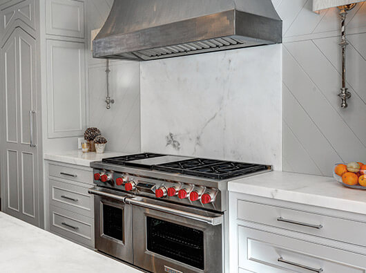 Sb-Zero stove and vent with a marble backsplash